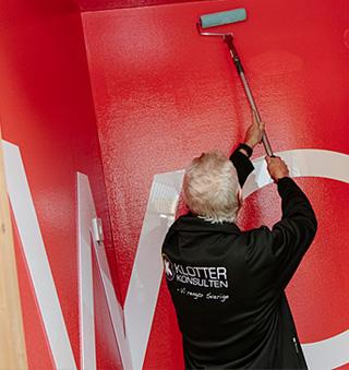 Man målar antistick på vägg.