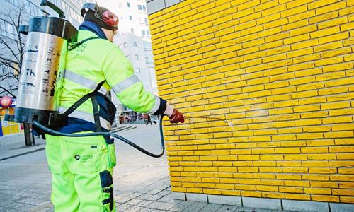 Man applicerar vaxklotterskydd på vägg.